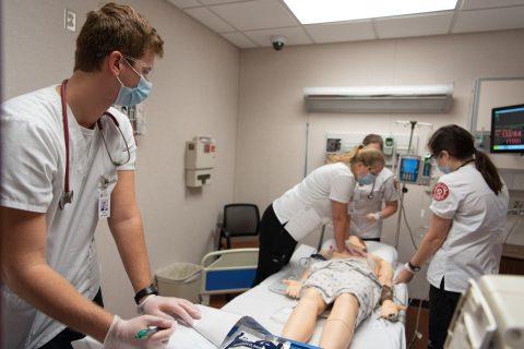 Students work on manikin in MCN's nursing simulation lab.