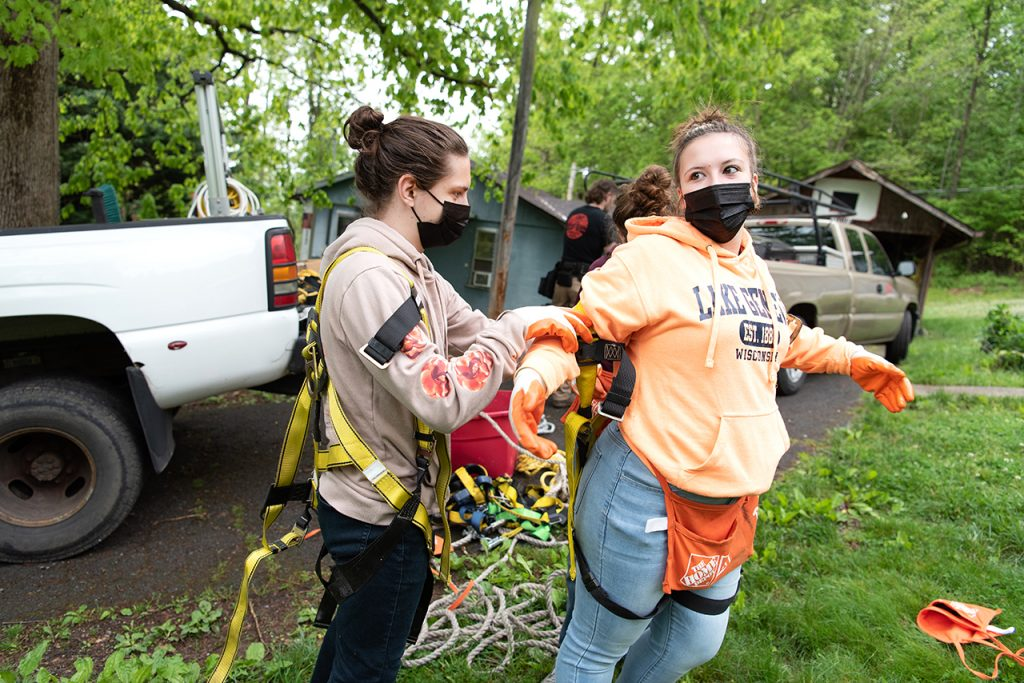 Sophomore philosophy major William Restis (left) helps senior sociology major Anna Raymond adjust her safety harness before heading up onto the roof for the first day of roofing a house.