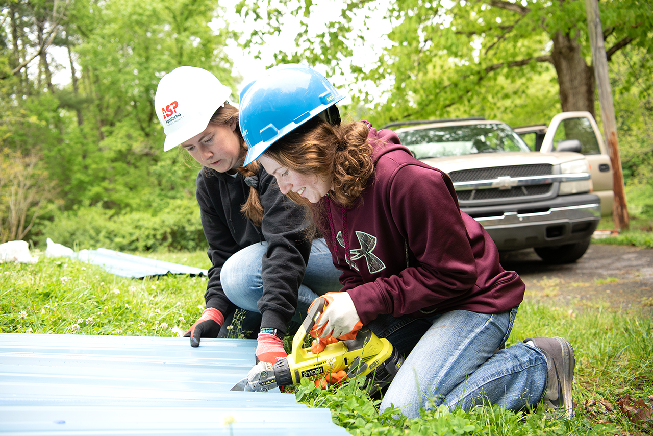 Senior agricultural communication major Katie Dowling (right) uses an electric cutting tool to trim down a sheet of tin roofing material as Caroline Nowak holds the piece steady.