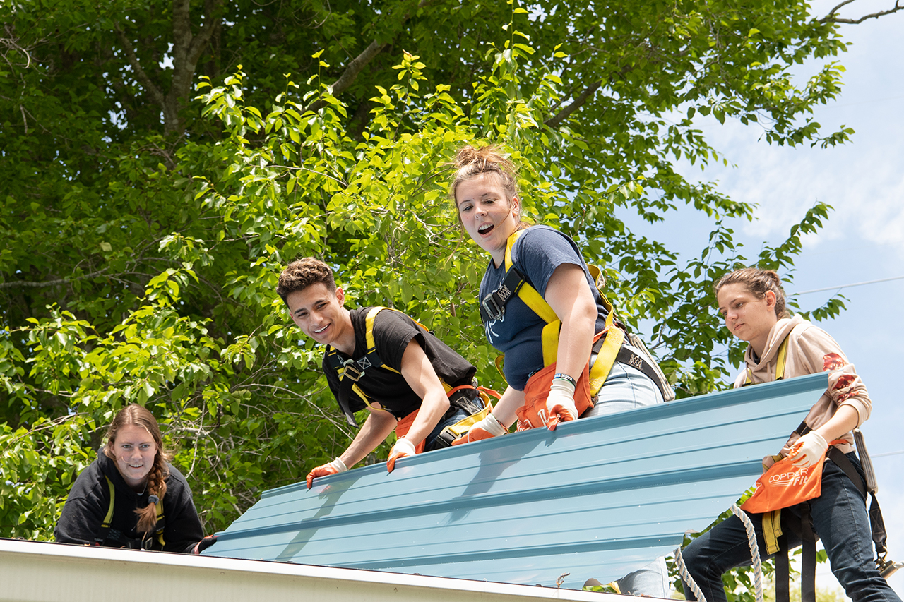 Anna Raymond and Victor Ventura set a new piece of tin roofing material into place on the roof as Nowack, far left, and Restis, far right, look on.