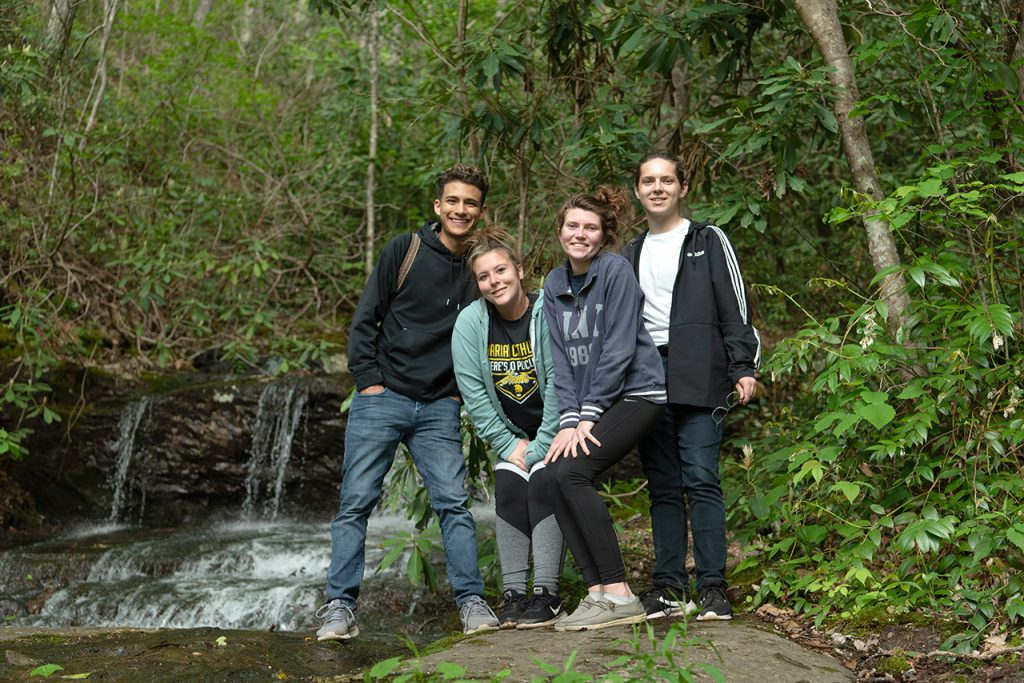 Victor Ventura (left), Anna Raymond, Katie Dowling, and William Restis pose next to a waterfall on the mountain in the woods that was adjacent to the house where they stayed at for the week in Elizabethton. They took a hike after work one day to explore the beauty that is east Tennessee.