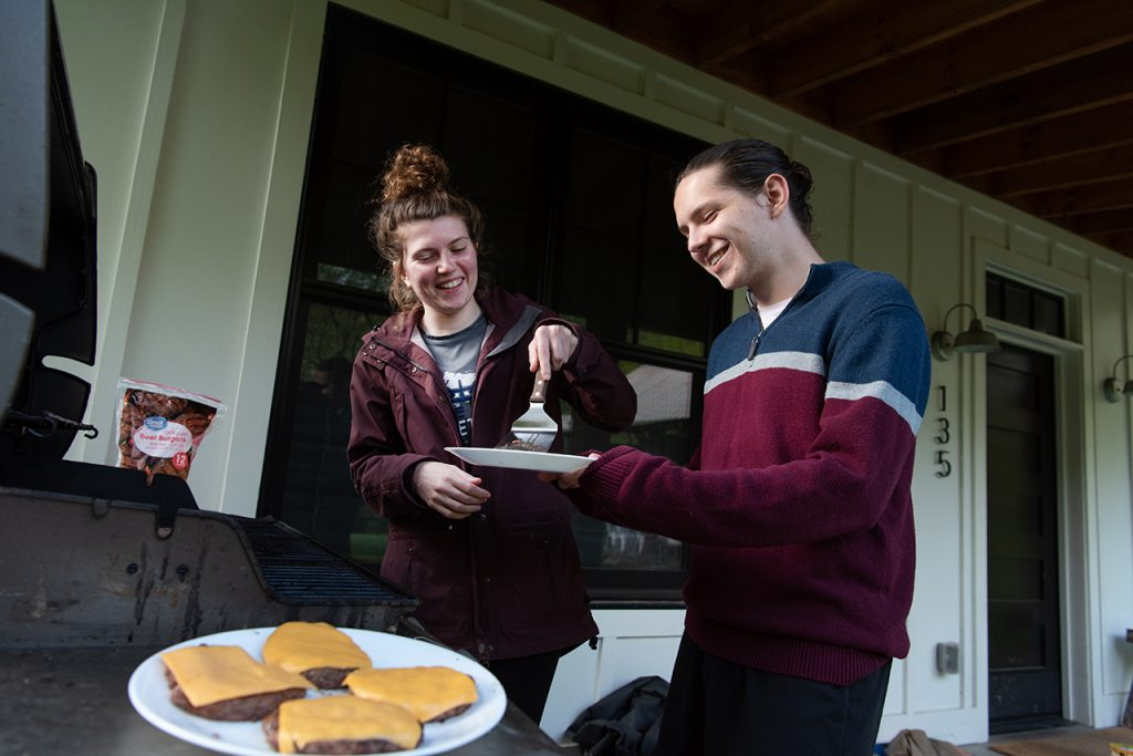 William Restis (right) holds the plate as Katie Dowling removes the cooked cheeseburgers from the grill in preparation for dinner.