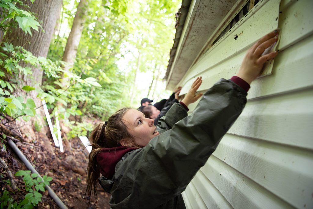 Anna Raymond lines up a piece of siding before sliding it into place on the back side of a house.