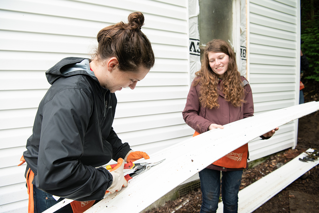 Katie Dowling (right) holds a piece of siding level as William Restis (left) uses a pair of tin snips to trim it down to fit around the under hang of the house.