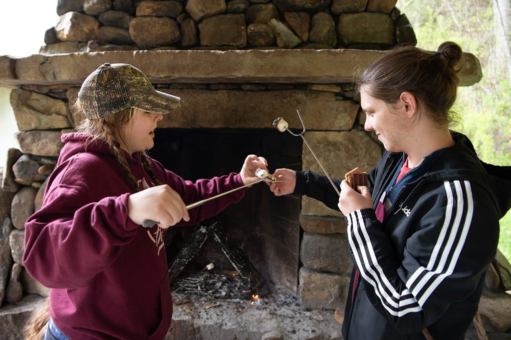 William Restis helps Anna Raymond remove her cooked marshmallow from the campfire stick to make s'mores for a late afternoon snack.