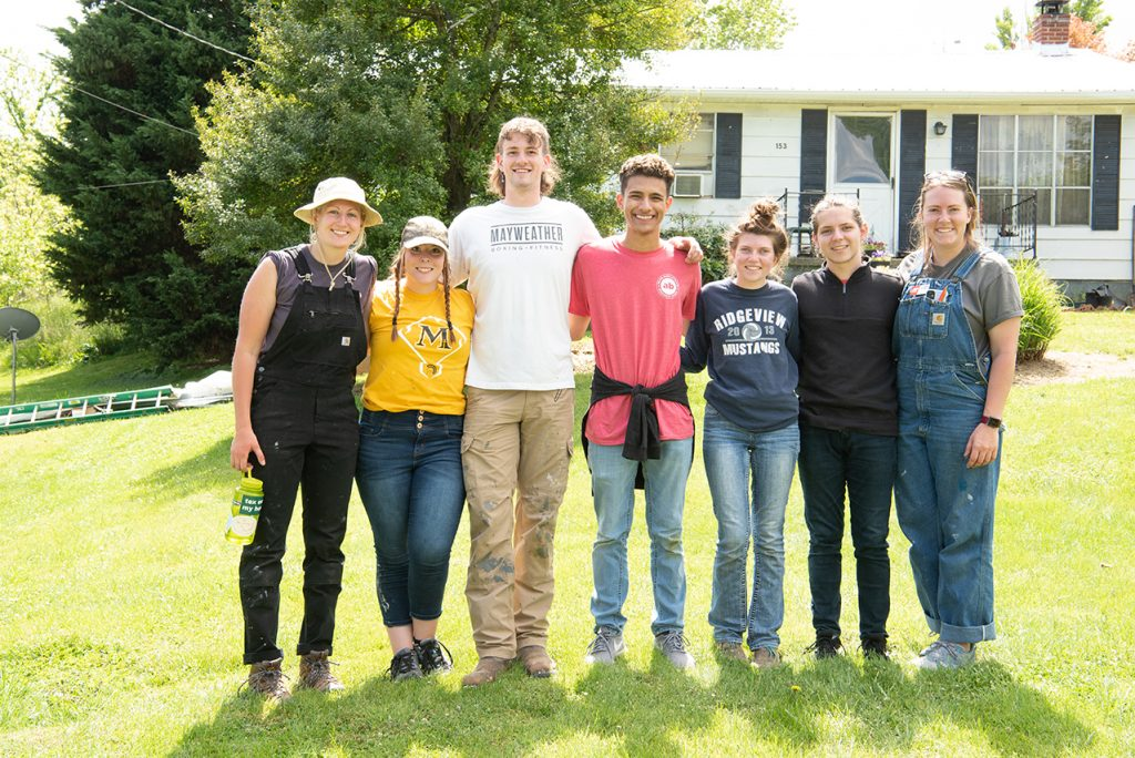 Rose Chelednik (left), of Tri-Cities Home Repair; Anna Raymond; Cameron Perry, liaison; Victor Ventura; Katie Dowling; William Restis; and Caroline Nowak pose for a photo on the last day of service in front of the final house they roofed together.