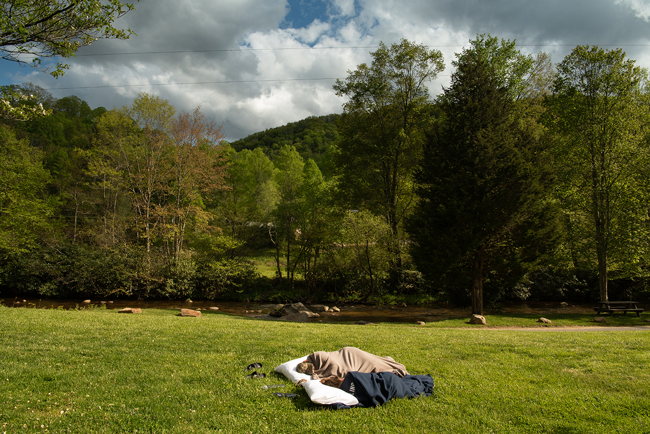 Tired from a long day of work, Anna Raymond and Katie Dowling take a nap in the front yard of the house on the mountain.