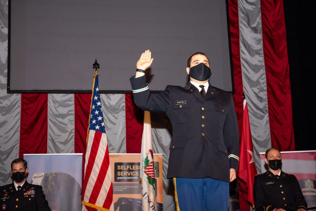Man in military uniform raises right hand in front of American flag