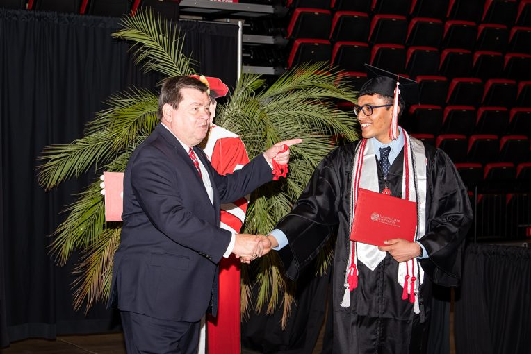 President Dietz shakes hand with a graduate