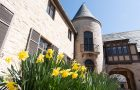 Side of Ewing manor with daffodils in the foreground