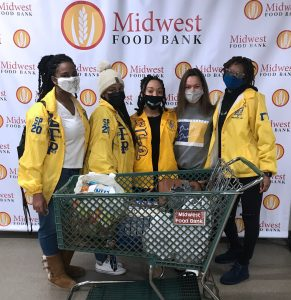 individuals in yellow jackets with green shopping cart