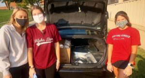 three individuals pose near a car trunk; the trunk contains packaged food