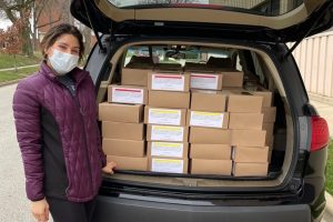 a student stands near the back of a car, packed with boxes of food for donation