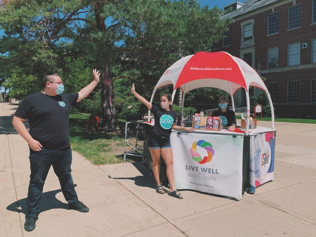 Leaders of Students Ending Rape Culture (SERC) high-five each other on the Illinois State Quad.