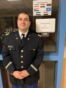 Man in uniform stands next to Department of English sign