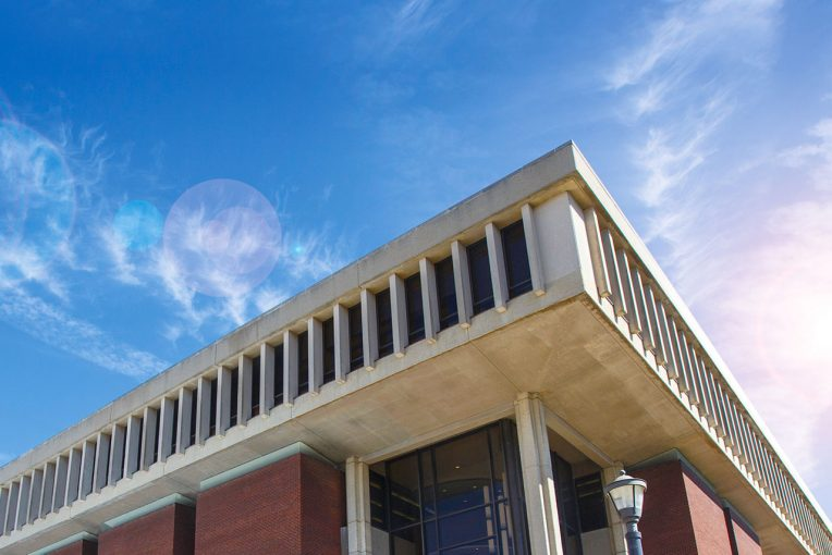 Corner of Milner Library's exterior building with blue sky and wispy clouds in the backgroud