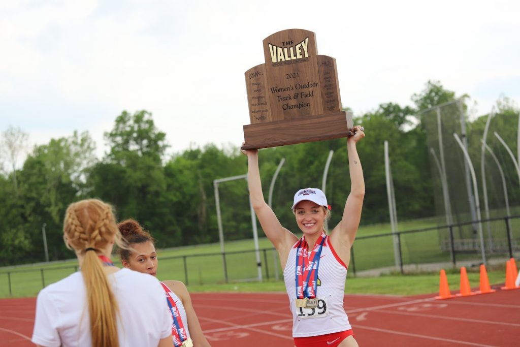 Woman triumphantly lifts trophy above her head