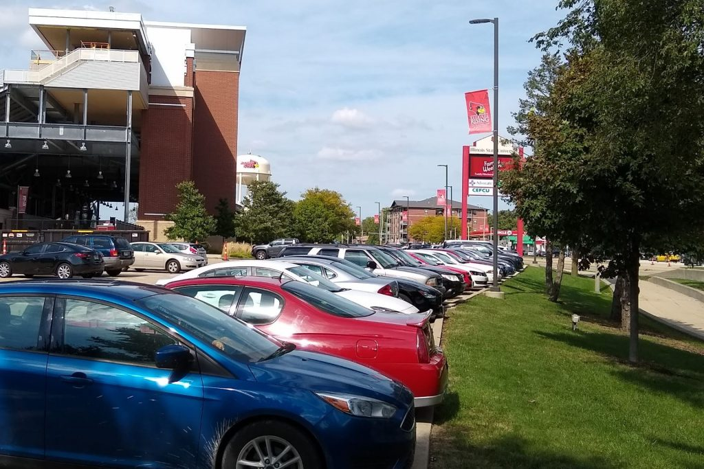 Row of cars in parking lot G73 in front of Hancock Stadium