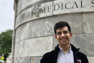 Basheer Becerra stands in front of Harvard Medical School sign.