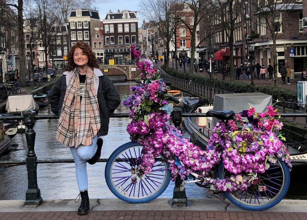 Study abroad student standing next to a bicycle covered in flowers on a bridge in Amsterdam.