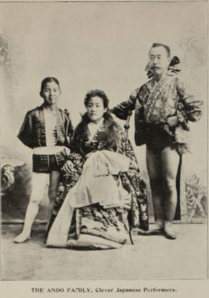 Photo of the Ando family circus performers with a woman sitting in a chair, a child standing to her right, and an adult male standing to her left