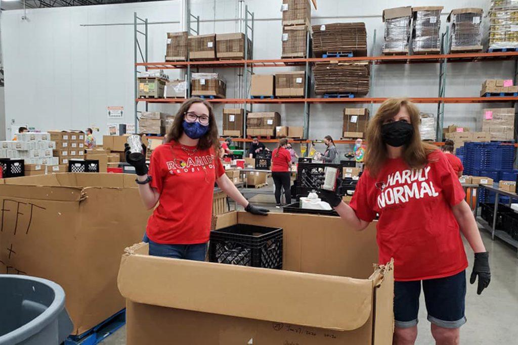 two women empty a large box