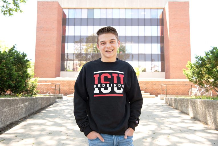 student posing in front of campus building