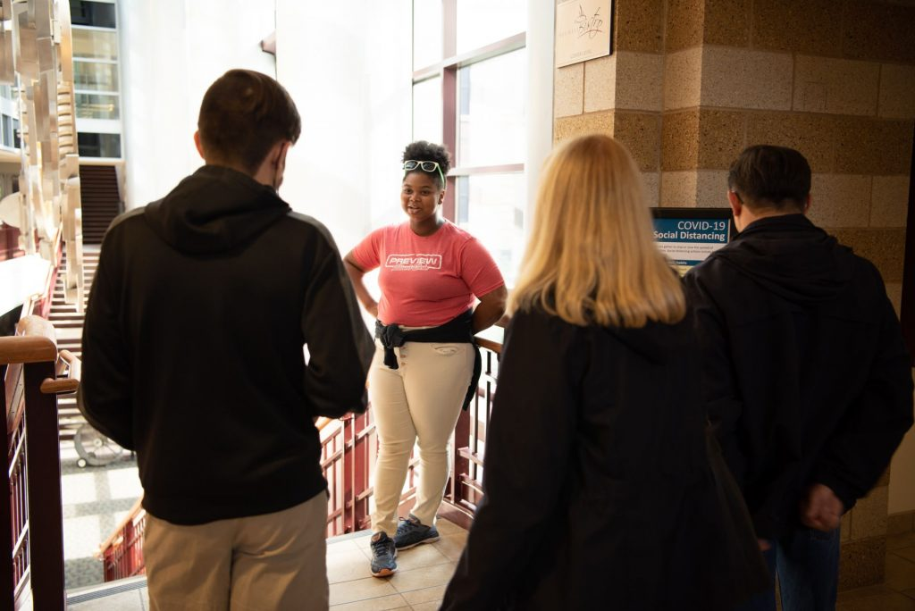 Woman in red shirt gives a tour to students and parents