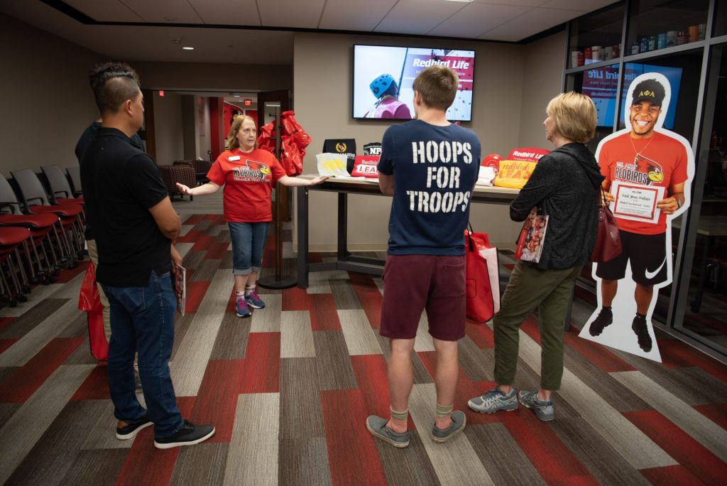 Woman talks with a group of students and their parents in front of a television screen and cardboard cutout.
