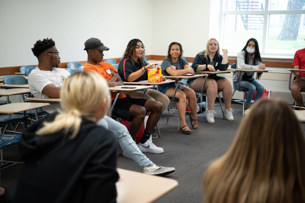 Woman seated in center of a room leads a conversation of first-year students.
