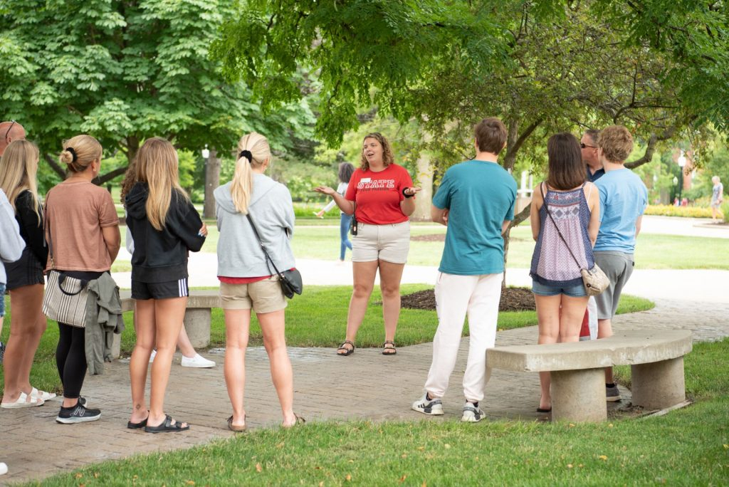 Preview guide gives a group of students and families a tour of the Quad.