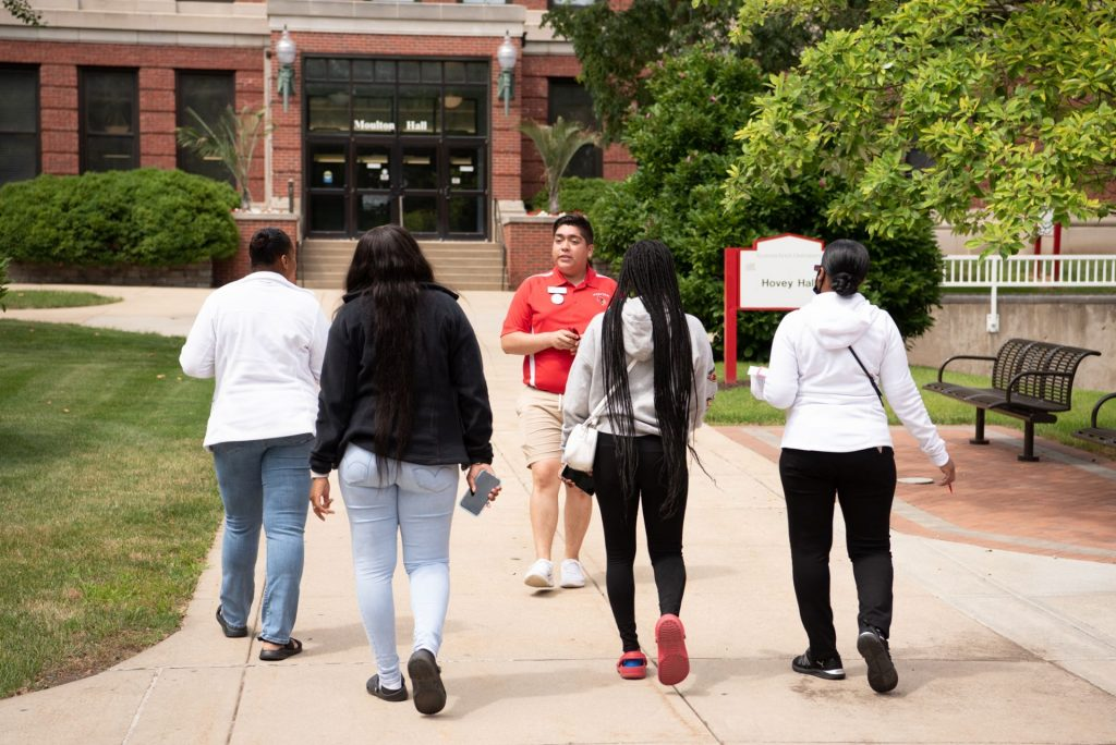 A Preview guide talks to a student and their family about what departments are located in each of the buildings during a tour of campus.