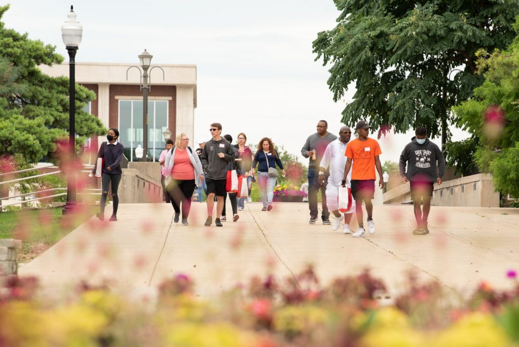 Students and their families walk across the bridge over College Avenue on their way to Edwards and Schroeder Halls for the morning sessions.