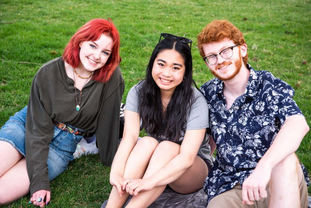 Three students enjoy some time on the Quad