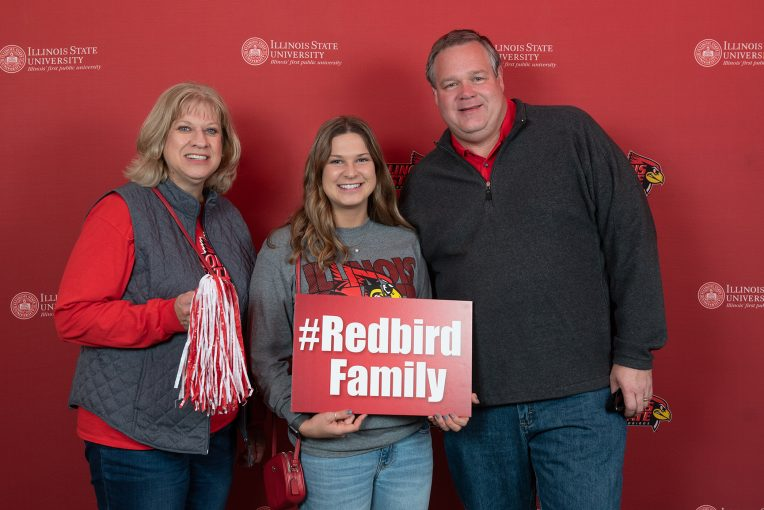 family posing together with ISU signs