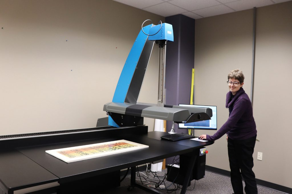 person stands in front of computer next to a large format scanner bed