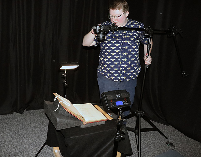 Person uses camera on a tripod and lighting apparati to photograph an old book for digitization.