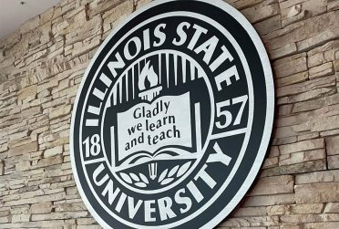seal of Illinois State University carved in wood wit the words Gladly we learn and teach