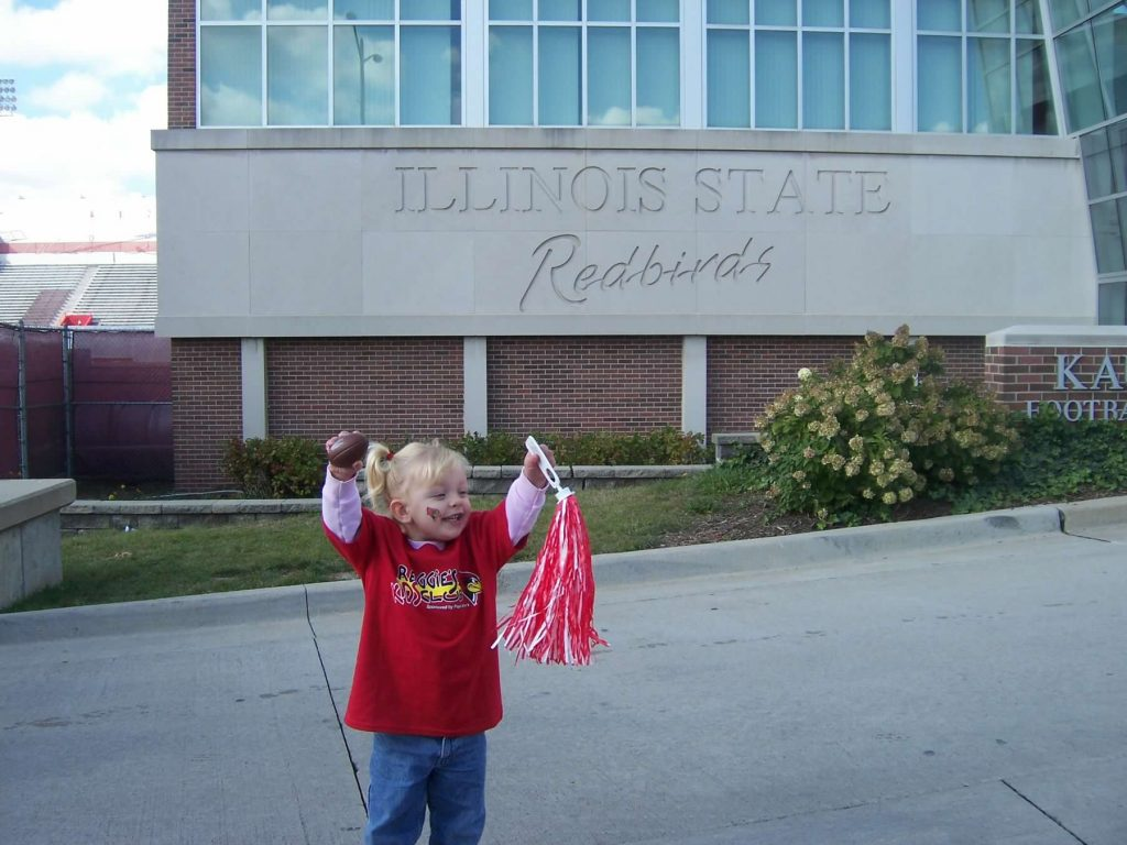 A little girl in a red shirt cheering with her arms up.