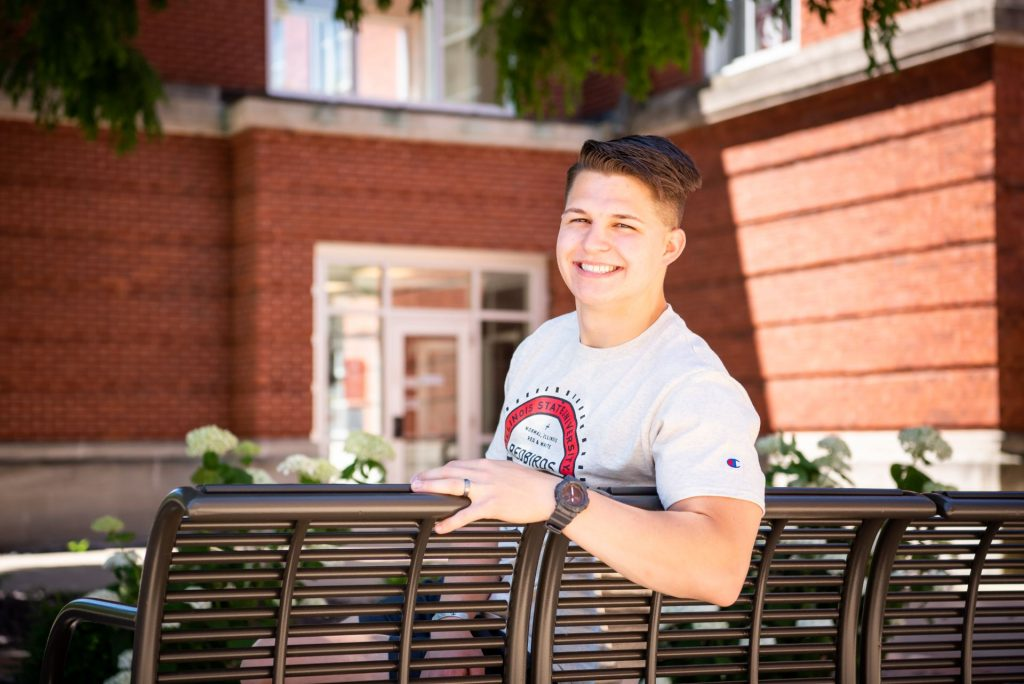 Male student sitting on a bench