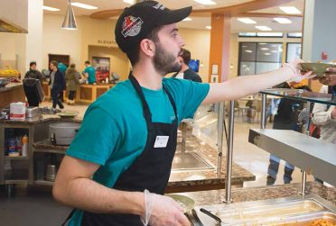 Dining Hall worker serving a customer