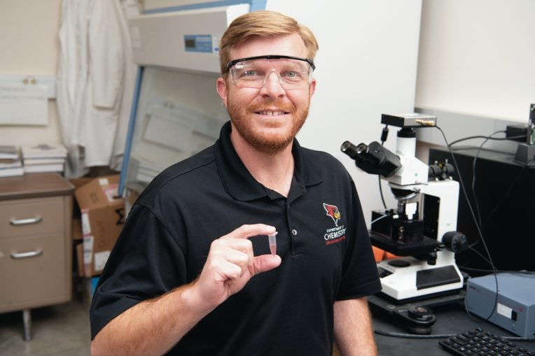 Dr. Jeremy Driskell holds object in lab