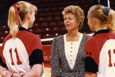 Woman in suit talking to two players in volleyball uniform