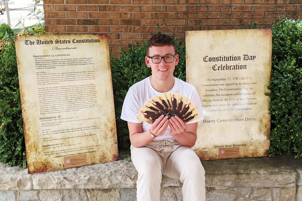 Joshua Crockett poses with copies of the Constitution