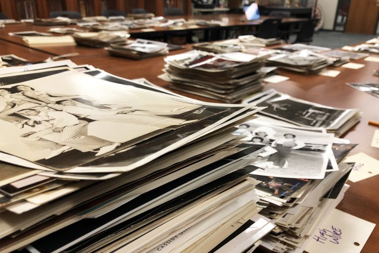 photograph of stacks of photographs sitting on a table in Special Collections' Reading Room