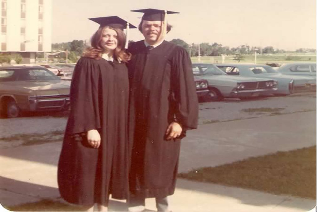 A man and a woman in graduation gowns.