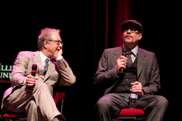 two men seated with microphones