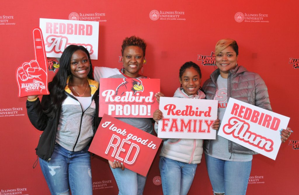 A Redbird family posing with spirit signs in front of a red Illinois State background