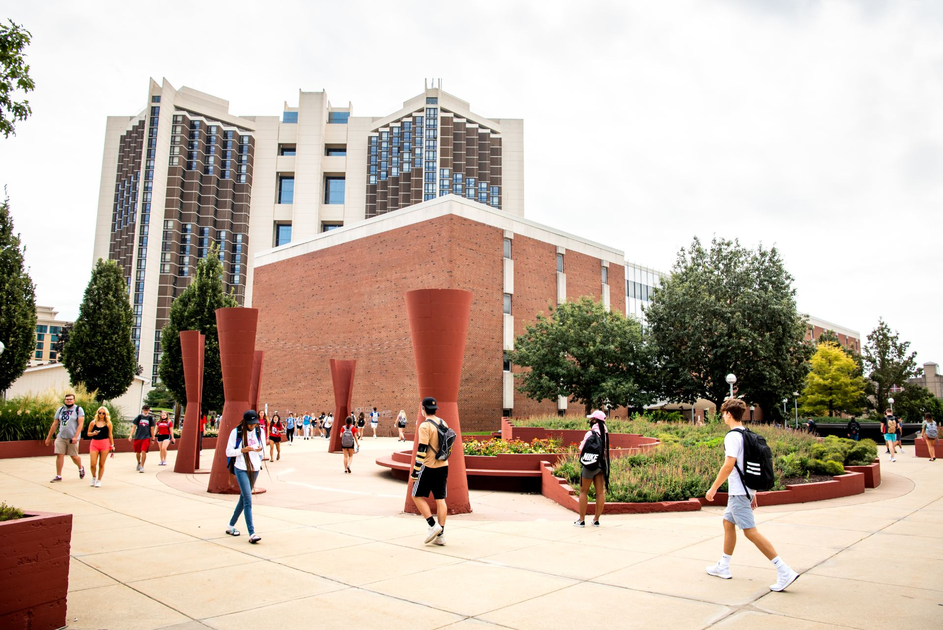 Campus sidewalks are bustling with students walking to classes between classes.