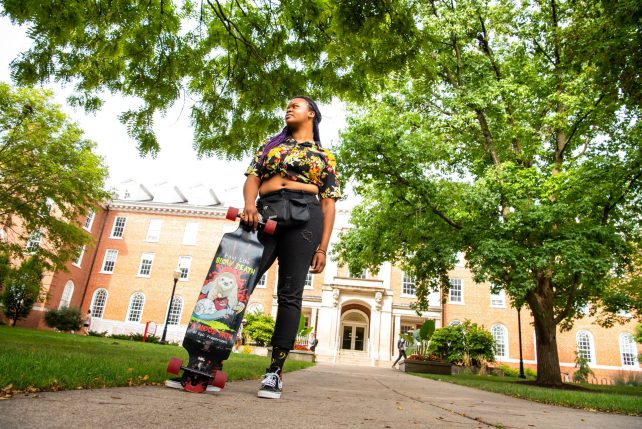 Music education and composition double major Miki McCarthy skateboards in front of Fell Hall on their way to class.